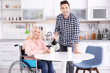 Young man taking care of mature woman in wheelchair indoors