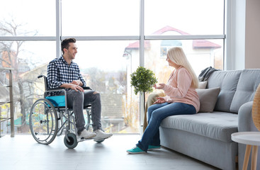 Mature woman talking to young man in wheelchair indoors