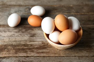 Bowl with chicken eggs on wooden table
