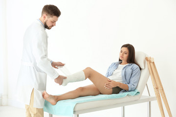 Doctor putting patient's leg in plaster  at clinic