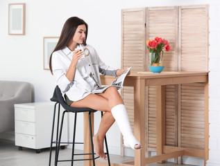 Young woman with broken leg in cast sitting on chair at home