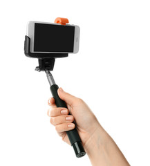 Woman holding selfie stick with mobile phone on white background