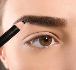 Young woman correcting eyebrow shape with pencil, closeup