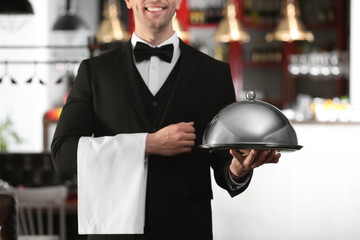 Waiter in elegant uniform holding metal tray and cloche at workplace