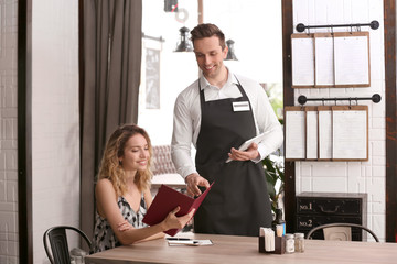 Young waiter taking order from client in restaurant