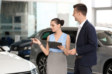 Young saleswoman working with client in car dealership