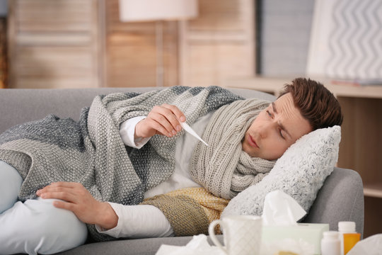 Sick young man with thermometer suffering from cold on sofa at home