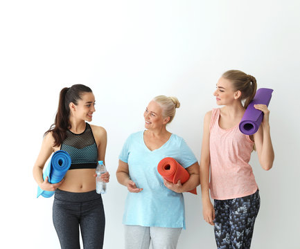 Women in sportswear with yoga mats on white background