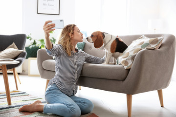 Young woman taking selfie with her dog at home