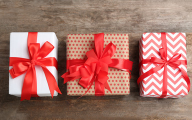 Different gift boxes on wooden background, flat lay