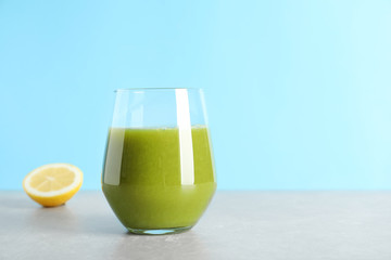 Glass with delicious detox juice and lemon on table