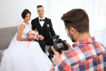 Professional photographer with camera and wedding couple in studio