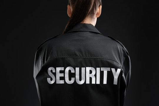 Female security guard in uniform on dark background, closeup