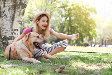 Young woman taking selfie with her dog outdoors. Pet care