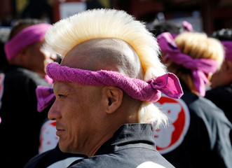 A man waits for his turn to carry a portable shrine, a Mikoshi, at the Senso-ji Temple during the Sanja festival in Asakusa district in Tokyo