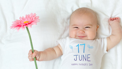 Father's Day message with baby girl holding a flower