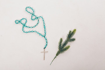 Spruce branch and wooden cross on blue beads on white background