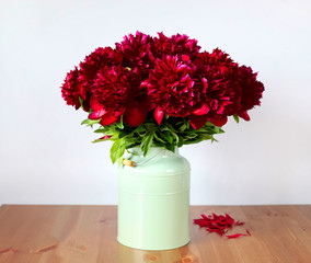 Maroon peonies in a vase on the table