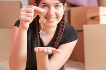 Image of young brunette with keys from apartment against blank wall
