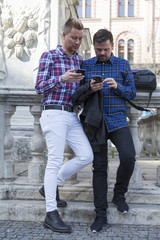 two men standing at a balustrade in the city streets playing with their gadgets exchanging data