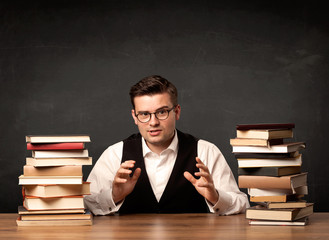 A young teacher in glasses sitting at classroom desk with pile of books in front of clean blackboard back to school concept.
