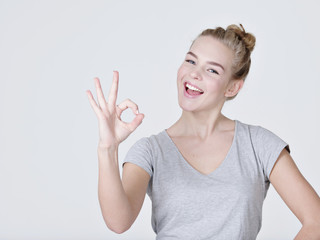 Beautiful young happy woman shows okay sign
