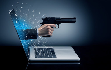 Hand with gun coming out of a laptop with sparkling effects