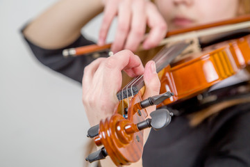 girl plays the violin, the hand puts the chord