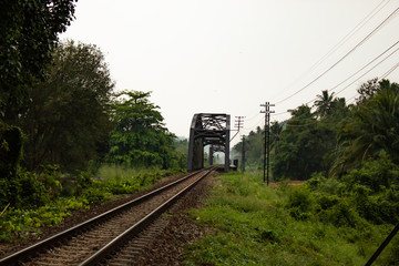 Iron bridge crossing the river and rail