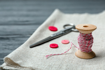 Composition with thread and sewing accessories on wooden background
