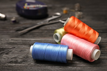 Sewing threads and accessories on wooden background