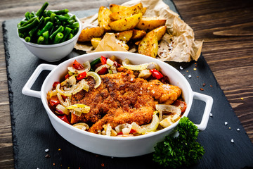 Fried pork chop with vegetables on wooden background
