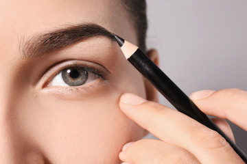 Young woman correcting eyebrow shape with pencil, closeup
