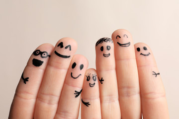 Fingers with drawings of happy faces against light background. Unity concept