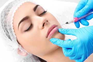 Young woman getting lip injection in beautician salon