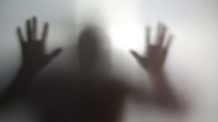 Silhouette of mad man against transparent wall, schizophrenia, addiction
