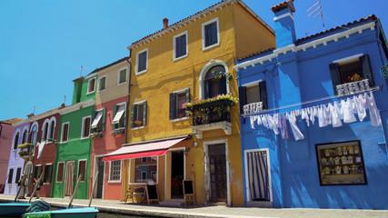 Travellers enjoying leisure trip, taking photo in colorful Burano island street