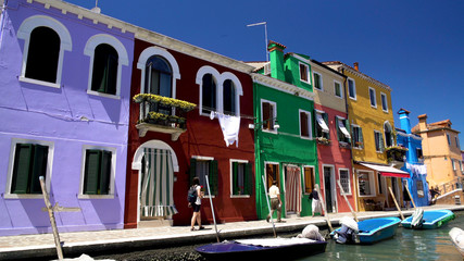 Curious tourists walking street on Burano island, photographing colored houses
