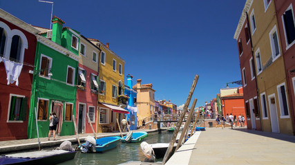 Many relaxed people strolling in colorful streets on Burano island, summer rest