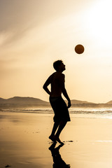 Silhouette of a man playing football (soccer) at sunset. Famara beach, Lanzarote, Canary Islands, Spain.