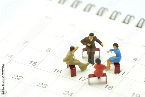 Miniature 4 People Sitting On Red Staples Placed On A White Calendar