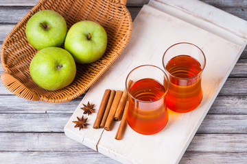 Apple juice in glasses, spices on wooden cutting table and apples in wicker basket
