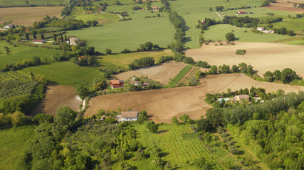 Aerial view of the countryside between Tuscany and Marche in Italy during a beautiful sunny day in summer. The fields are cultivated and the hills are rich in trees and forests.