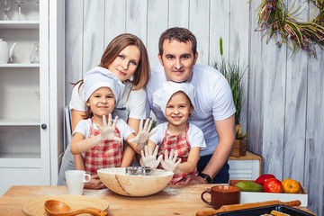 Family happy mom, dad and two girls twin sisters in the kitchen bake cookies from flour.