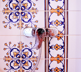 Closeup of shiny shower faucet with waterdrops and  beautiful tiles in background