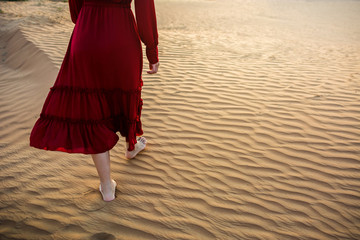 Woman walking in the desert at sunset