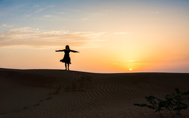 Silhouette of a woman in the desert at sunset