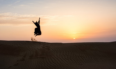 Silhouette of a woman jumping in the desert