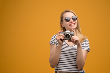 Cheerful hipster girl with retro camera on a yellow background