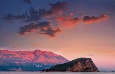 View of Sveti Nikola island and budva riviera at sunset. Dramatic evening sky. Montenegro, Adriatic sea, Europe.